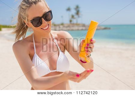 Woman pouring sun protection cream in hand