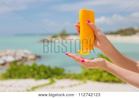 Woman holding yellow sunscreen bottle in hands