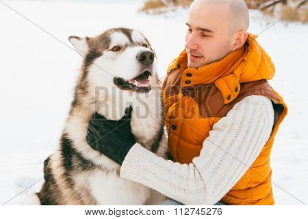 Man Walking With Dog Winter Time With Snow In Forest Malamute Friendship