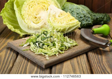 Cut savoy cabbage on wooden cutting board closeup
