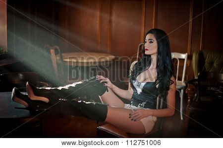 Beautiful sexy girl with long leather boots sitting on chair relaxing with legs on the table