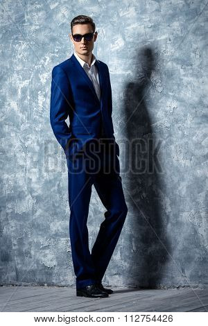 Full length portrait of a fashionable handsome young man in elegant classic suit and sunglasses.