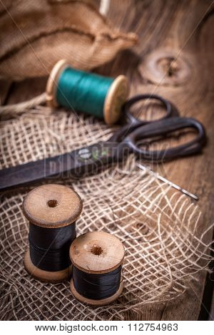 Old Sewing Kit On The Wooden Table.