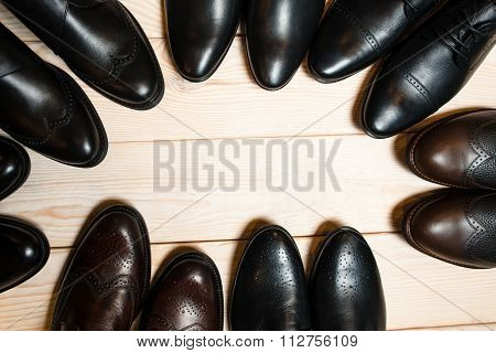 Many Leather Men's Shoes On Wooden Background