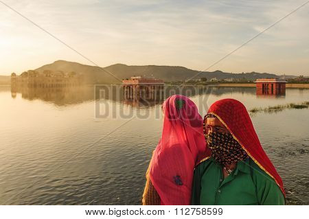 A local women visiting The palace Jal Mahal at sunrise.