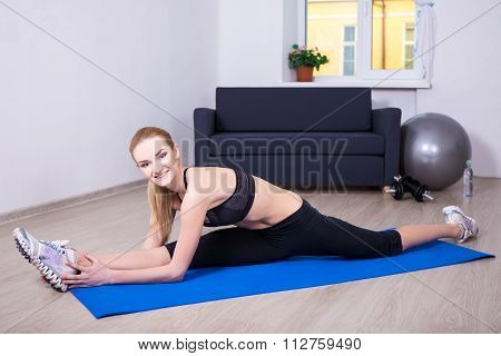 Beautiful Flexible Woman Doing Stretching Exercise On Yoga Mat At Home