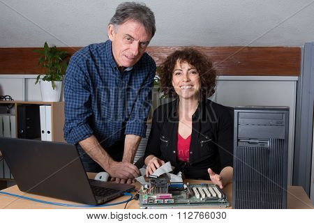 Team Of Technicians Working Together Repairing Computer