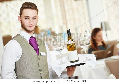 Waiter occupation. Young man with wine bottle and glasses on tray servicing in restaurant