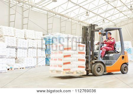 warehousing. Forklift driver stacking pallets with cement packs by stacker loader
