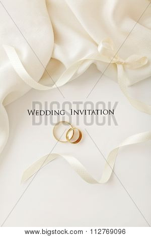 two wedding rings and wedding invitation