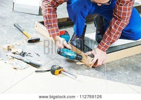 Carpenter joiner worker preparing door frame for indoor installation
