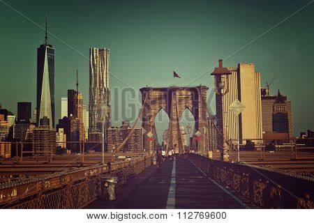 Toned artistic view of Brooklyn Bridge pedestrian walkway with the tower and steel suspension cables against a backdrop of the modern architecture of New York City