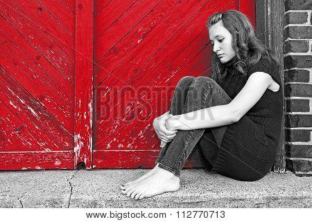 depressed teenage girl by red door