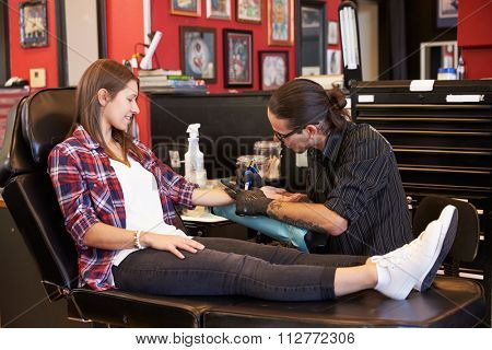 Woman Sitting In Chair Having Tattoo On Arm In Parlor