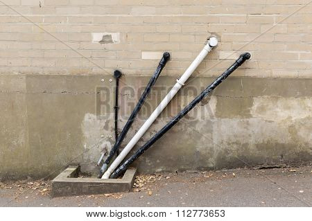A Photo Of Black And White Angular Water Pipes On A Beige Brickwork Wall