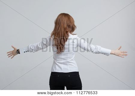 woman stands back and raised her arms to the side, on grey background