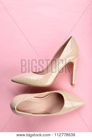 Pair of beige women's high-heeled shoes on pink background