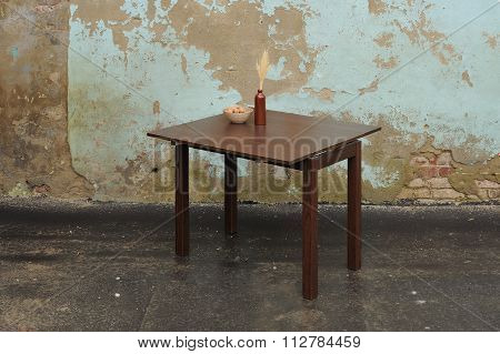 Woden Table With Vase And Wallnuts Near Old Plastered Wall