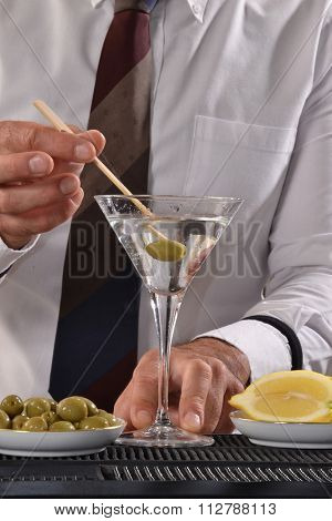 Barman adding olive to martini cocktail drink.