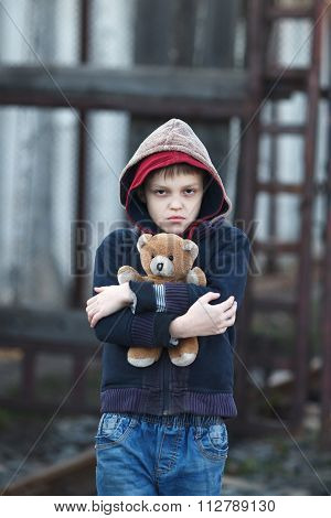 Dramatic Portrait Of A Little Homeless Boy Holding A Teddy Bear