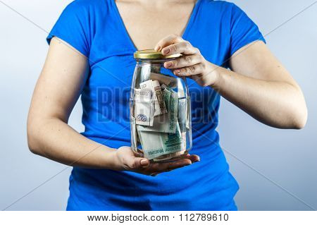 The woman holding jar with Russian money