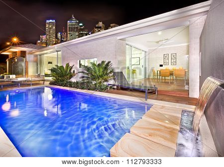 A Moody And Stylish Image Of A House Pool With Beautiful City Behind The House In Night