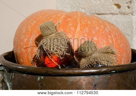 Pumpkin With Bottles Of Potions In A Copper Vat On Wall Background. Close-up.