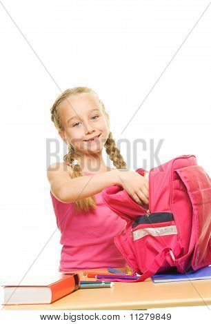 Little beautiful happy schoolgirl packing her rucksack