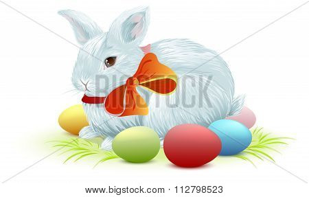 White easter bunny sitting on green grass. Bunny and colored Easter eggs