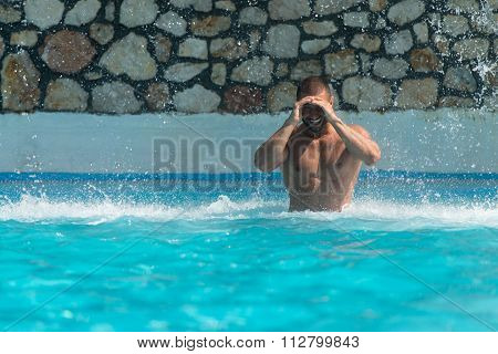Muscular Man Standing Under A Water