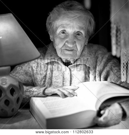 An old woman reads a book, night lamp, black and white photography.