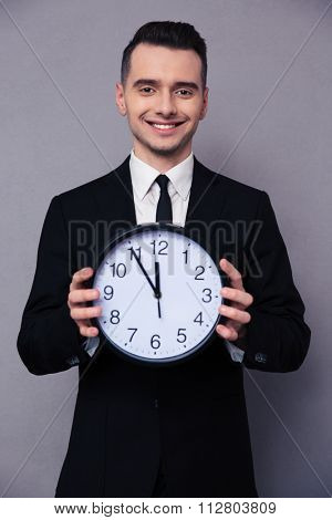 Portrait of a smiling businessman holding wall clock over gray background