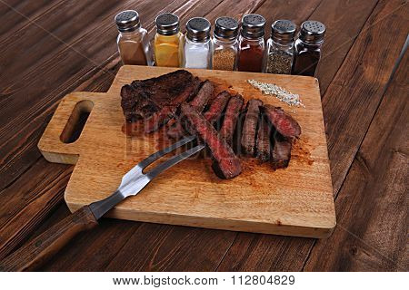 grilled beef fillet steak on fork over wooden board served with different kind of dry spices salt crushed black pepper hot baked sweet paprika red hot chili on dark table