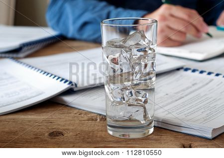 Glass Of Water With Ice On A Wooden Office Teble