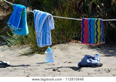 Still picture of towels drying on the beach on a rope