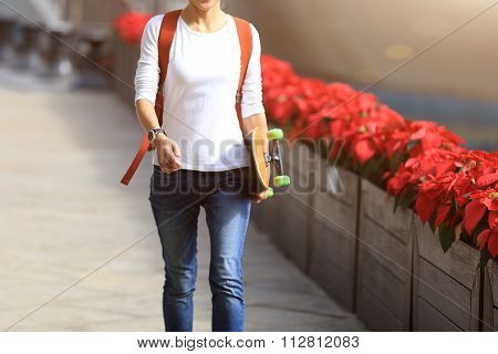 one young woman walking with skateboard at city