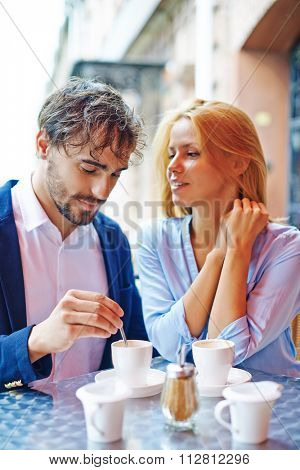 Affectionate couple drinking coffee together at a cafe