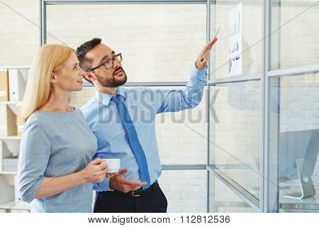 Businessman showing financial graphs to his colleague