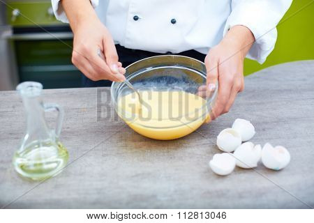 Close-up of male hands mixing eggs in bowl