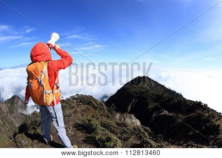 young woman successful on mountain peak shout with loudspeaker
