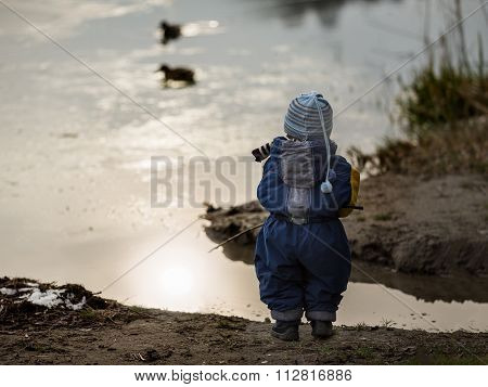 Little Boy Playing Outdoor On Frozen Lake Shore.