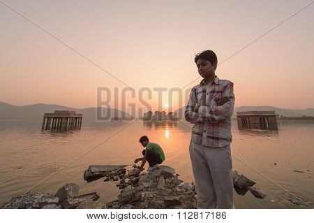 Local people visiting the palace Jal Mahal at sunrise.