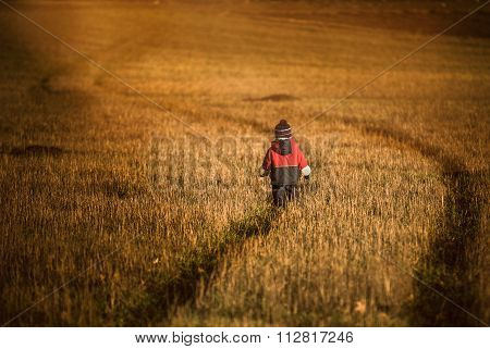 Little Boy Playing Outdoor On Stubble Field