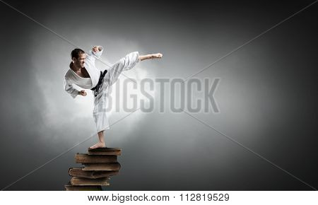 Young determined karate man on pile of books