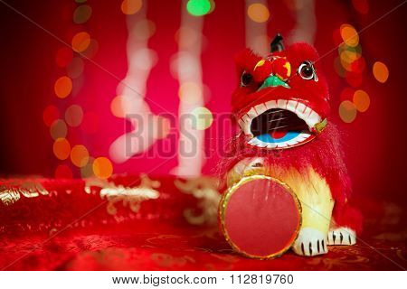 Chinese new year festival decorations, miniature dancing lion on red glitter background.