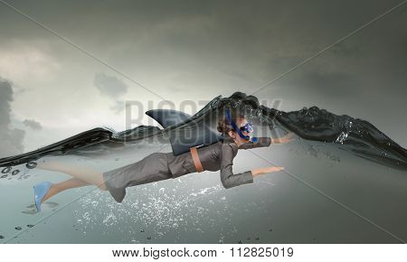 Young businesswoman with shark flipper swiming under water