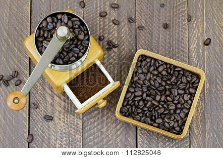Vintage wooden coffee hand grinder with ground coffee inside next to a wooden box full of very dark roasted Robusta coffee beans