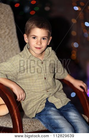 Little boy in rock chair at home on a blurred background