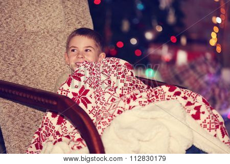 Little boy in rock chair with plaid at home on a blurred background