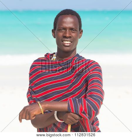 Traditonaly dressed black man on beach.